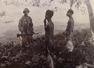 KNIL-soldaat bij ontklede gevangenen