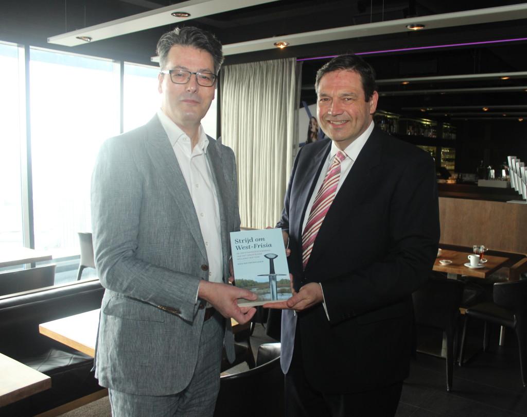 Auteur Kees Nieuwenhuijsen overhandigt het boek aan gedeputeerde Rik Janssen