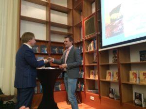 Hugo Koning overhandigt het eerste exemplaar van zijn nieuwe boek aan collega Bert van den Berg (Universiteit Leiden).